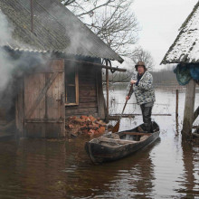 Seto Culture from Voru County, Estonia man standing and paddling wooden boat between houses on lake